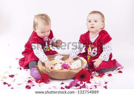 identical twin sisters playing with a wooden bowl of sand, rose and gerbera petals.