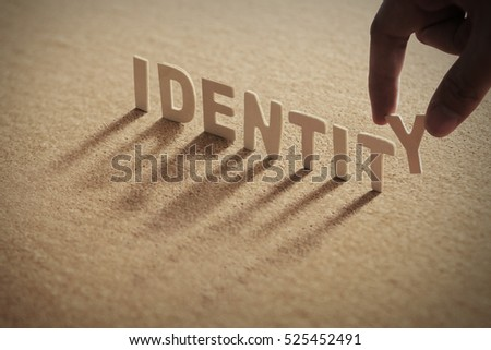 IDENTITY wood word on compressed board with human's finger at Y letter