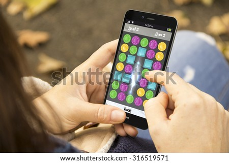 idle and gaming concept: girl playing a jigsaw game on a digital generated smartphone. All screen graphics are made up. - stock photo