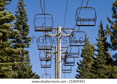 Idle lift chairs between row of evergreen trees - stock photo