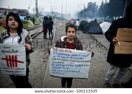 Idomeni, Greece - March 15, 2016. Children from Syria hold banners, as stranded refugees demonstrate, in the makeshift camp at the northern Greek village of Idomeni at the Greek-Macedonian border.