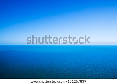 Idyllic abstract background - horizon line between calm sea and clear blue sky - stock photo
