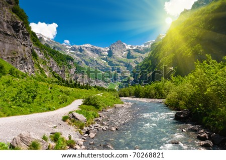 Idyllic alpine valley with mountain river and hiking trail in sun rays. Sixt Fer a Cheval national reserve, France. - stock photo