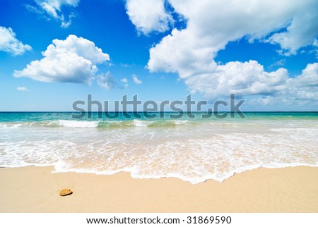 Idyllic beach with blue sky and fluffy white clouds - stock photo