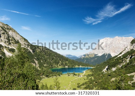 idyllic blue mountain lake in austrian alps with blue sky - stock photo