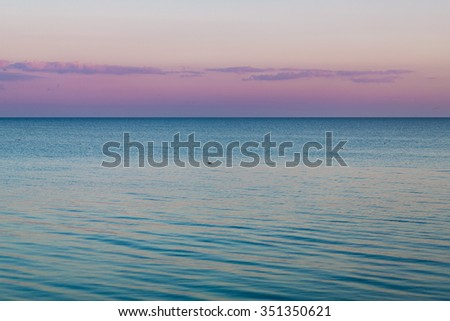 Idyllic calm sea horizon nature landscape wallpaper with seagulls on the water - evening in pastel blue ocean and pink cloudy sky colors at background - stock photo