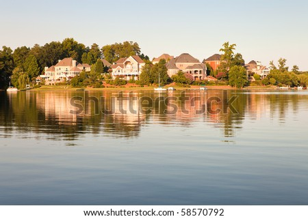 idyllic countryside view with lake and house on sunset - stock photo