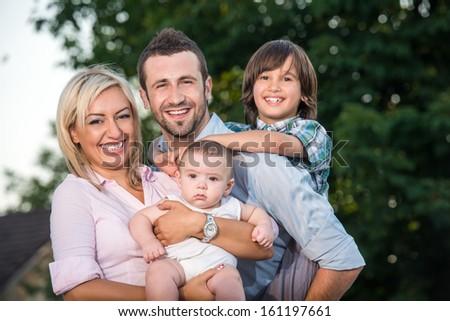 Idyllic happy family scene outdoors - stock photo