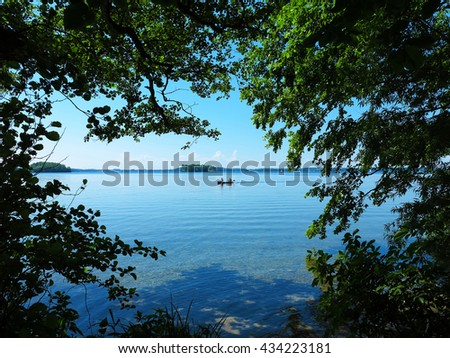 idyllic lake view with boat and islets - stock photo