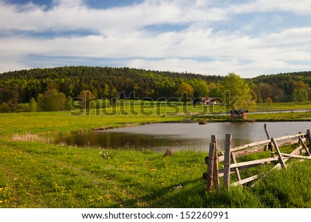 idyllic landscape in springtime with fish farming lake - stock photo