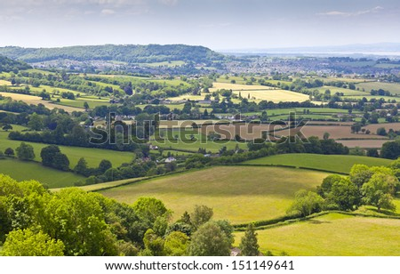 Idyllic rural view of gently rolling patchwork farmland and villages with pretty wooded boundaries, in the beautiful surroundings of the Cotswolds, England, UK. - stock photo