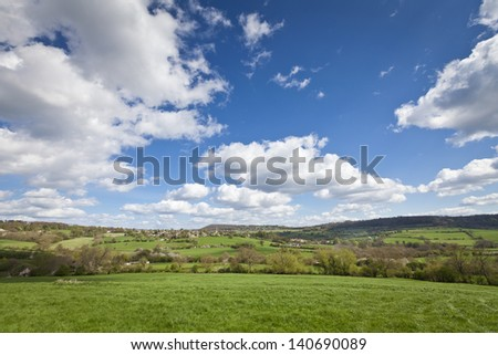 Idyllic rural view of pretty farmland and white fluffy clouds, in the beautiful surroundings of the Cotswolds, England, UK. - stock photo