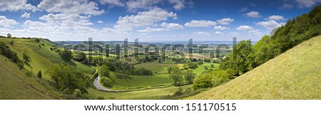 Idyllic rural view of pretty farmland with white fluffy clouds, in the beautiful surroundings of the Cotswolds, England, UK. - stock photo