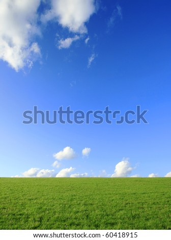 idyllic scene of field with blue sky and clouds - stock photo