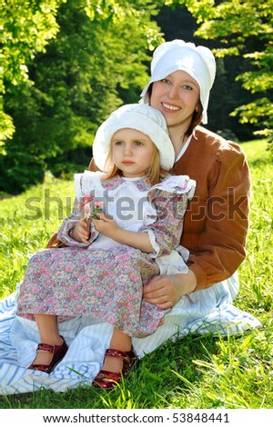 Idyllic scene with mother and little daughter in historic dresses on sunny meadow - stock photo