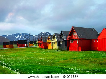 Idyllic scenic view, colorful houses and green field with arctic flowers against the background of dramatic sky and barren mountain in Longyearbyen, Spitsbergen archipelago (Svalbard), Norway, Europe - stock photo