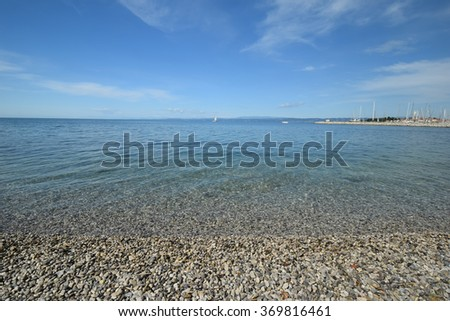 Idyllic seascape, blue sky and sea water. Seascape background - Adriatic pebble beach - stock photo