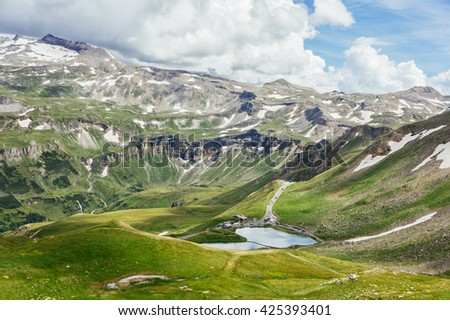 Idyllic summer view with clear mountain lake and mountain peaks in snow in Austria Alps. Summer mountain landscape with snowy peaks and green grass valley near mountain lake. Mountain lake landscape. - stock photo