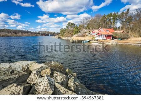 Idyllic Swedish house on the sea coast - stock photo