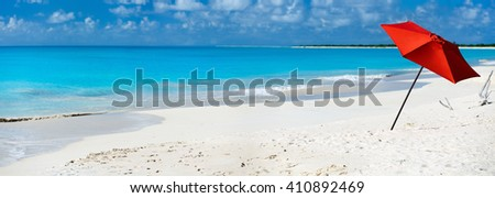 Idyllic tropical beach with red umbrella, white sand, turquoise ocean water and blue sky at deserted island in Caribbean - stock photo