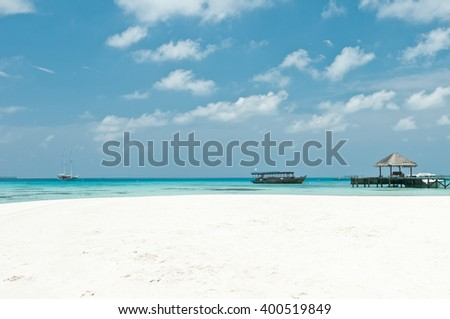 Idyllic tropical beach with white sand, turquoise ocean water, blue sky, boat, bridge and clouds at Maldives - stock photo