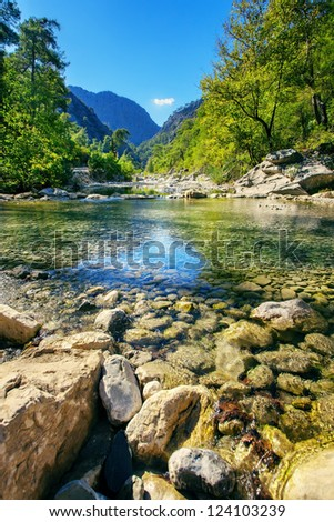 Idyllic valley with mountain river - stock photo