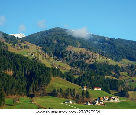 Idyllic view on alpine hills with green grass coniferous forest and small alpine houses on a sunny summer day  - stock photo
