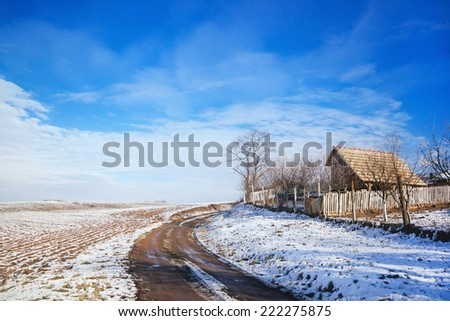 Idyllic winter scene with house and snow covered fields - stock photo