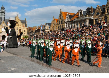 IEPER, BELGIUM - MAY 13, 2012: People dressed in Ieper cat costumes walk in front of spectators tribunes on the 43th edition of the Cat Parade in Ieper, Belgium on May 13, 2012 - stock photo