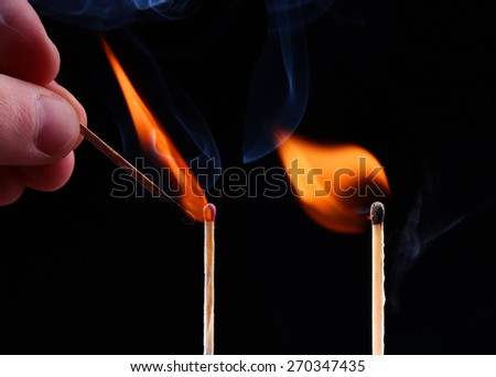 Ignition of a match, with smoke on dark background. Hand holding burning match stick