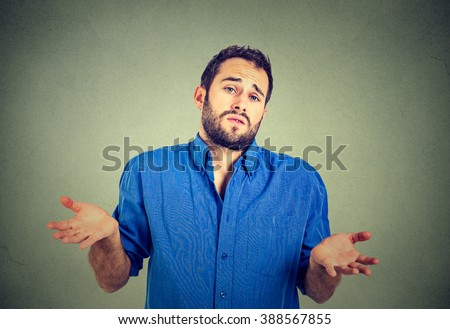 Ignorance and arrogance. Closeup portrait young man shrugging shoulders who cares so what I don't know gesture isolated on gray wall background. Human body language. Whatever attitude reaction   - stock photo