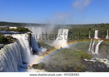 Iguassu waterfalls with rainbow on a sunny day. The largest waterfalls on earth - stock photo