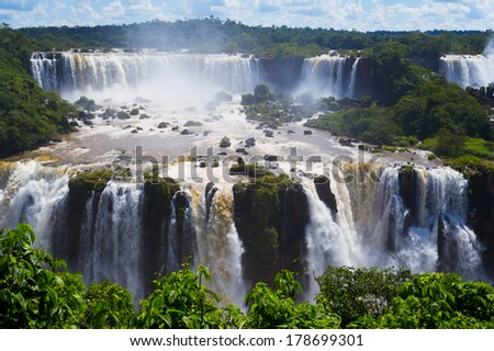 Iguazu Falls or Iguassu Falls in Brazil. Beautiful Cascade of waterfalls with clouds and jungle