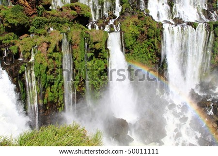 Iguazu waterfalls with rainbow on a sunny day. The largest waterfall on earth - stock photo