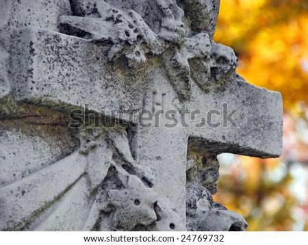 ihs marked cross statue in autumn cemetery - stock photo