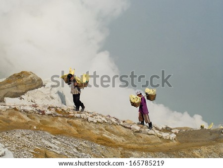 IJEN VOLCANO, INDONESIA - JAN 10:Workers carry sulfur inside crater on January 10, 2011 in Ijen Volcano, Indonesia. They carry the load of around 60kg to the top of the crater and then 3km down.  - stock photo