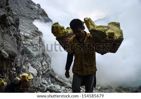 IJEN VOLCANO, INDONESIA -24 JULY 2013: Worker carrying sulfur inside Ijen crater on July 24, Indonesia. He carries the load of around 60kg to the top of the rip and then 3km down. - stock photo