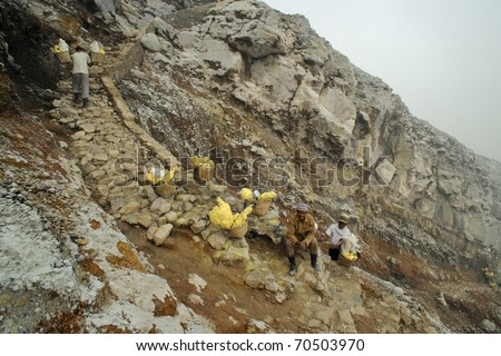 IJEN VOLCANO, INDONESIA - JUNE 29: Worker carrying sulfur inside Ijen crater on June  29, 2010 in East Java, Indonesia. He carries the load of around 90kg to the top of the rip and then 3 km down. - stock photo