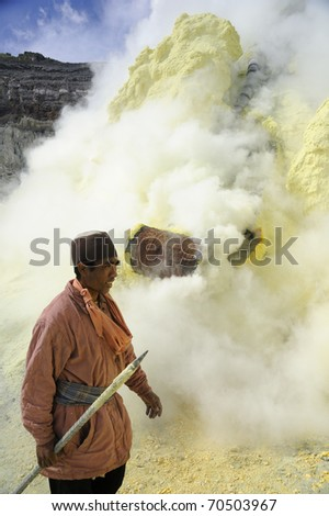 IJEN VOLCANO, INDONESIA - JUNE 29: Worker extracting sulfur inside Kawa Ijen crater on June 29, 2010 in East Java, Indonesia. People are working in really awful conditions. - stock photo