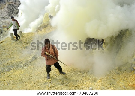 IJEN VOLCANO,INDONESIA - JUNE 29: Workers are extracting sulphur inside Kawa Ijen crater on June  29, 2010 in East Java, Indonesia. People are working in really awful conditions. - stock photo