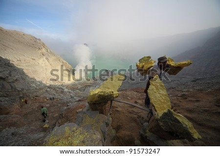 IJEN VOLCANO, INDONESIA - SEPT 18:Worker carry sulfur inside Ijen crater on Sept 18, 2011 in East Java, Indonesia.Miners are paid USD6 for every 100kg they bring out from the inner crater to basecamp - stock photo