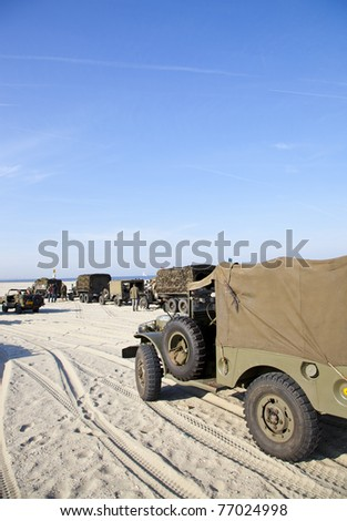 IJMUIDEN, THE NETHERLANDS-MAY 5: Army trucks of organization Kelly's Heroes riding on beach on May 5,2011 in IJmuiden, The Netherlands. Simulate arrival of allies on liberation Second World War