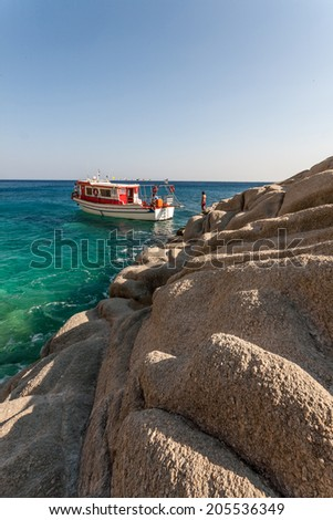 IKARIA ISLAND, GREECE - AUGUST 23, 2007: People work in a cruise boat, preparing the vessel for the next trip destination, as part of their daily job, during summer, in order to make a living. - stock photo