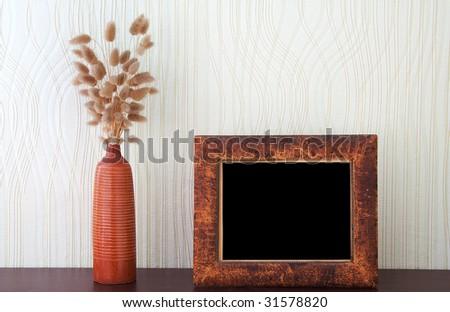 ikebana and vintage photo-frame on table - stock photo