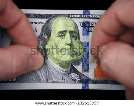 Ill Bill. Benjamin Franklin Looking Sickly On The United States One Hundred Dollar Bill With Two Hands Hesitant Along Side Over Black Background. - stock photo