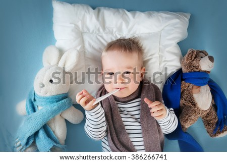Ill boy lying in bed - stock photo