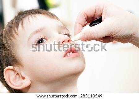 ill boy with flu and drops in the nose - stock photo