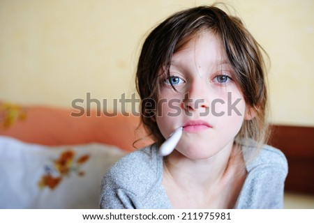 Ill child girl sitting in the bed and holding thermometer - stock photo