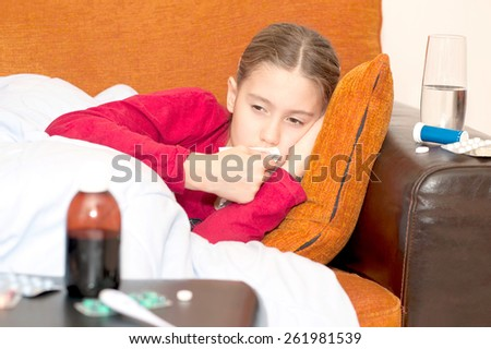 Ill child lying on a sofa with handkerchief. Indoors. - stock photo