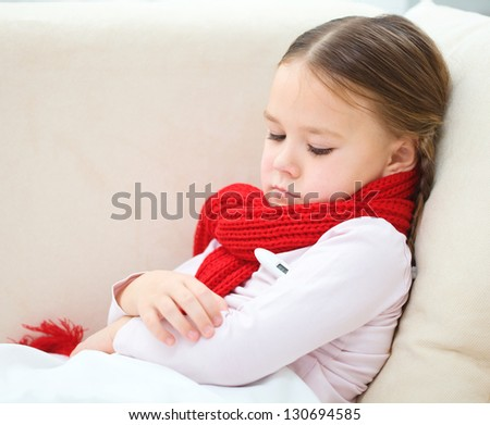 Ill little girl is laying on sofa with thermometer under her arm - stock photo